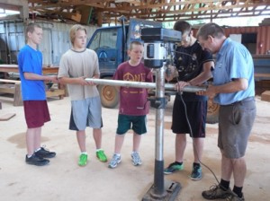 Bobby, Ben and Timothy hold the pipe while Nate drills with supervision from Ron